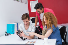 Smiling students working with camera together Stock Images