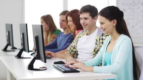 Smiling students working with computers at school Royalty Free Stock Images