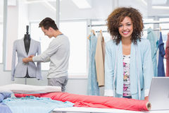 Smiling students working with fabric and model Royalty Free Stock Photo