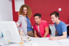 Smiling students working together on computer Stock Photography