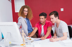 Smiling students working together on computer Royalty Free Stock Photos