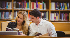 Smiling students working together while sitting at table Royalty Free Stock Images