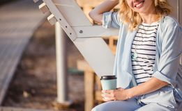 Smiling stylish blond woman drinking coffee outside on street background. Space for text. royalty free stock photography