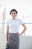 Smiling stylish brown haired businesswoman posing looking at camera Stock Photos