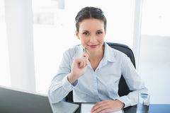 Smiling stylish brunette businesswoman looking at camera and holding a pen Stock Photos