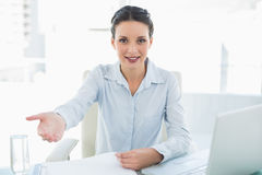 Smiling stylish brunette businesswoman presenting her hand Stock Photography