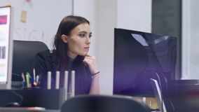 Smiling stylish brunette works at a computer. Business woman in a modern office