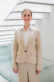 Smiling stylish businesswoman standing next to stairs Stock Photo