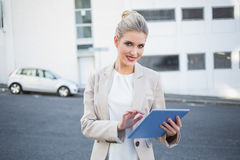 Smiling stylish businesswoman using digital tablet stock photos