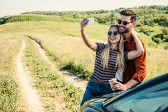 smiling stylish couple in sunglasses with coffee cup taking selfie on smartphone near car on rural stock images