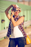 Smiling stylish girl posing with retro film camera on street Stock Photography