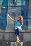 Smiling stylish girl is taking selfie against business center Stock Image