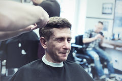 Smiling stylish man in a barbershop enjoys the process of his ha Stock Photos
