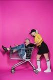 Smiling stylish senior woman pushing shopping trolley with joyful senior man having fun. Side view of smiling stylish senior women pushing shopping trolley with Stock Image