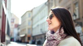 Smiling stylish travel girl in sunglasses enjoying break on narrow street holding paper coffee cup