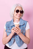 Smiling stylish woman holding an icecream. Stock Photo