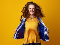 Smiling stylish woman against yellow background jumping Royalty Free Stock Photo