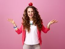 Smiling stylish woman on pink background with an apple on head. Pink Mood. smiling stylish woman with long wavy brunette hair on pink background with an apple on Stock Images