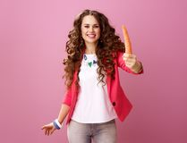 Smiling stylish woman on pink background showing carrot Stock Images