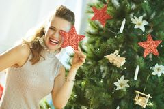 Smiling woman playing with Christmas star near Christmas tree stock images