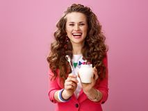 Smiling stylish woman showing farm organic yogurt and spoon. Pink Mood. smiling stylish woman with long wavy brunette hair isolated on pink background showing stock images