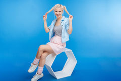 Smiling stylish woman sitting on modern chair Stock Photo