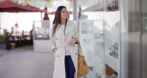Smiling stylish woman walking past a shop