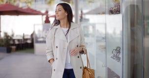 Smiling stylish woman walking past a shop Stock Photo