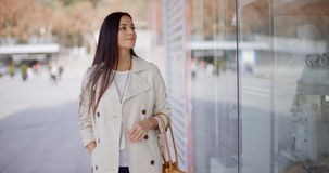 Smiling stylish woman walking past a shop Royalty Free Stock Photos