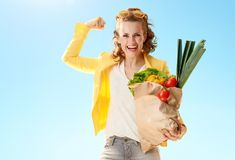 Woman with paper bag with groceries showing biceps again. Smiling stylish woman in yellow jacket with paper bag with groceries showing biceps against blue sky royalty free stock photography