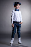 Smiling stylishly dressed boy posing in ice skates. On gray background Royalty Free Stock Images