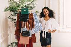 Smiling stylist standing at her wardrobe royalty free stock photo