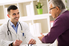 Smiling success doctor listening carefully his senior patient Royalty Free Stock Photo