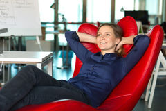 Smiling successful Business Lady in red relaxation Office Chair. Inside modern creative Company Office Royalty Free Stock Images