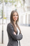 Smiling successful business woman looking at camera in the street. Royalty Free Stock Photos