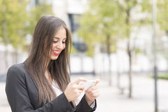 Smiling successful business woman using smart phone in the street. Royalty Free Stock Image