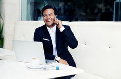 Smiling successful businessman sitting in modern expensive restaurant with open laptop and cup of coffee Royalty Free Stock Photography