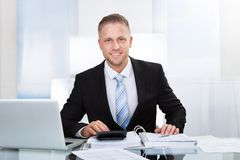 Smiling successful businessman st his desk. Smiling successful businessman sitting st his desk in the office surrounded by paperwork using a calculator and a Stock Images