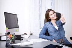 Smiling successful woman giving a thumbs up royalty free stock image