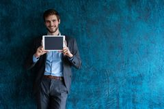 Smiling successful young businessman on blue background in a classic gray suit presenting a tablet. Smiling successful young businessman on blue background in a royalty free stock images