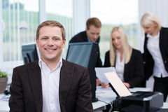 Smiling successful young businessman. In a busy office posing in the foreground for the camera Royalty Free Stock Photography