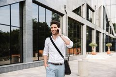 Smiling successful young businessman. Dressed white shirt walking outdoors, talking on mobile phone stock photo