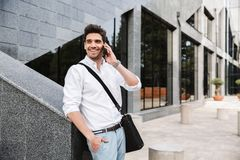 Smiling successful young businessman. Dressed white shirt walking outdoors, talking on mobile phone royalty free stock photos