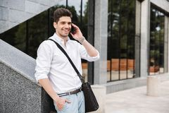Smiling successful young businessman. Dressed white shirt walking outdoors, talking on mobile phone stock photos