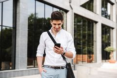 Smiling successful young businessman. Dressed white shirt walking outdoors, using mobile phone stock photography