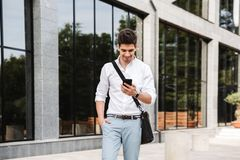 Smiling successful young businessman. Dressed white shirt walking outdoors, using mobile phone stock photo