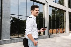Smiling successful young businessman. Dressed white shirt walking outdoors, using mobile phone royalty free stock image