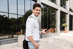 Smiling successful young businessman. Dressed white shirt walking outdoors, using mobile phone stock image