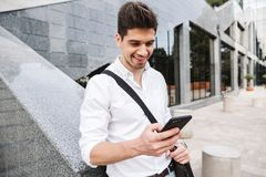 Smiling successful young businessman. Dressed white shirt walking outdoors, using mobile phone stock images