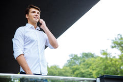 Smiling successful young businessman talking on cell phone Royalty Free Stock Image